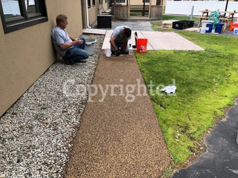 Our team installing rubber flooring for a pool deck